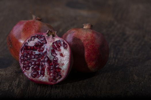 three pomegranades on dark wood