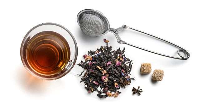 Black tea with natural aromatic additives and accessories. Top view on white background.