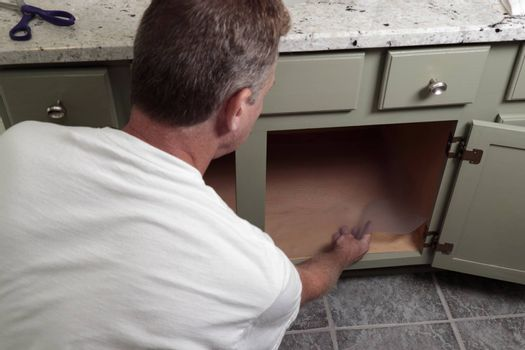 In a home bathroom inside a green painted wood cabinet a man lines the bottom of a bathroom cabinet with a plastic sheet. Clear plastic shelf liner being put on the bottom of a home bathroom cabinet.