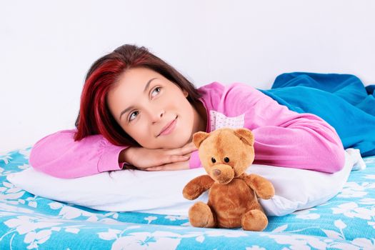 Beautiful young girl in pink pajamas lying in bed with her cute plush teddy bear daydreaming of something nice.