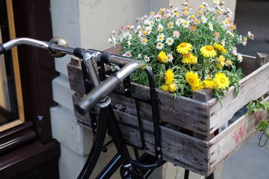 Black bicycle with wooden crate carrying flowers
