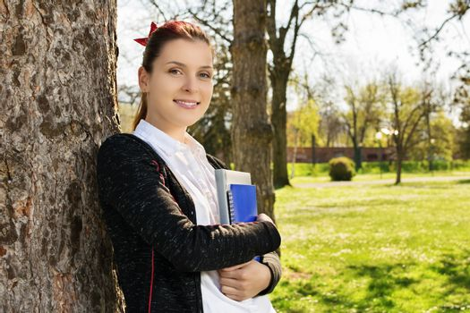 Beautiful casual student girl holding notebooks leaning against a tree in the park. Student taking a break from studying in the park.