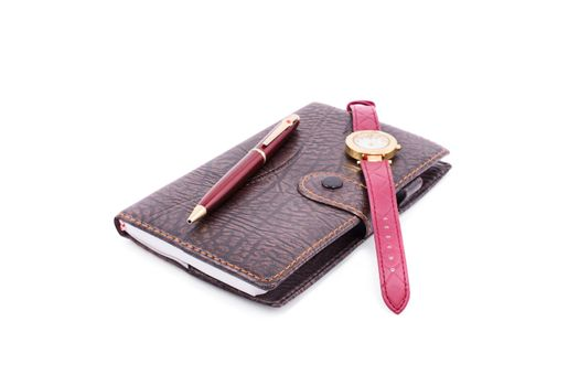 Close up of a planner notebook with a pen and wrist watch, isolated on white background.