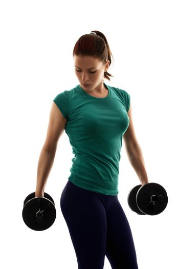Fit attractive young woman working out with a set of dumbbells, looking down, with a dramatic light, isolated on white background. Fitness and healthy lifestyle concept.