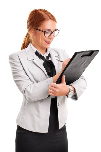 Portrait of a beautiful smiling young fashionable businesswoman writing on a clipboard, isolated on white background.