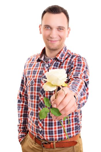 Portrait of a smiling handsome young man handing out a white rose flower to the camera, isolated on white background. Valentine's day, romance, love concept.