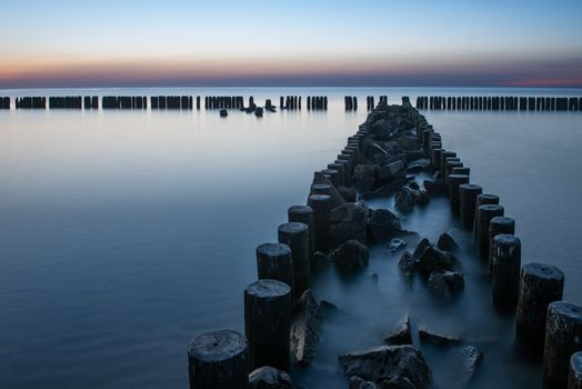 A photograph of wooden breakwater and seagulls at sunset on the Baltic Sea