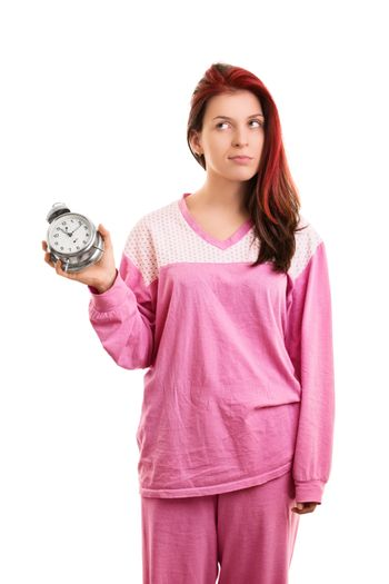 Portrait of a beautiful young girl in pink pajamas holding an alarm clock looking annoyed that she needs to get up, isolated on white background.