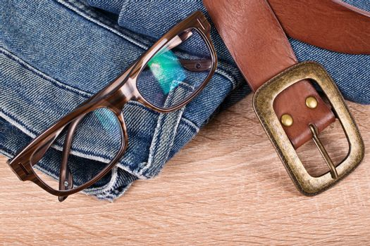 Close up shot of a pair of jeans, glasses and a leather belt on a wooden background.