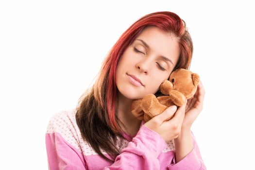 Close up of a young beautiful girl in pink pajamas hugging a plush brown teddy bear, isolated on a white background.
