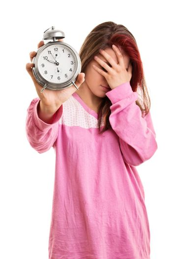 Being late concept. Close up of a young woman in pink pajamas holding an alarm clock and covering her face with her hand, looking tired and annoyed, isolated on white background.