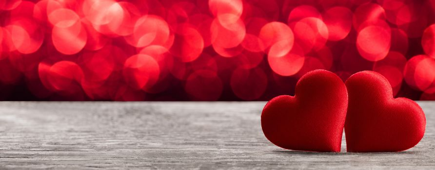 Valentine's day two red silk hearts on wooden background and bokeh lights, love concept