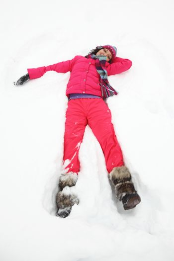 Beautiful joyful young woman in pink clothes laying down on a snow on vacation during a sunny winter day