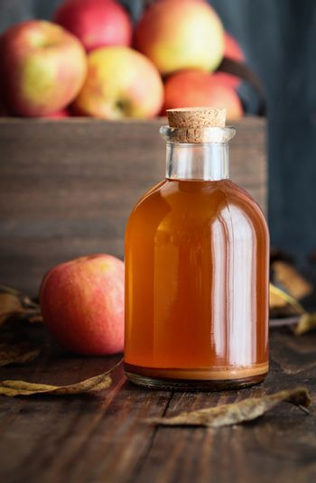 Apple Cider Vinegar with a Box of Fresh Apples