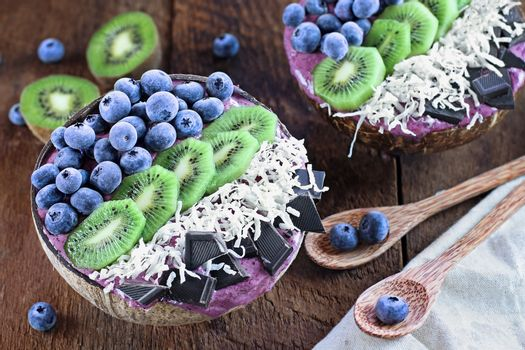 Açai smoothie bowl with fresh kiwi, frozen blueberries, organic coconut and dark chocolate pieces with wooden spoons served in coconut bowls over a rustic table. Shot from above / overhead with selective focus and blurred background.