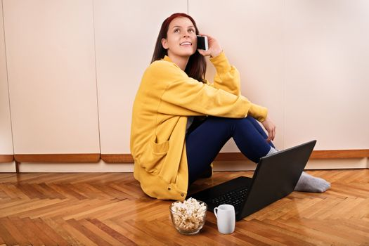 Communication, friendship concept. Girl talk concept. Beautiful young woman sitting on the floor in her room in front of her laptop with coffee and popcorn, and talking on the mobile phone.