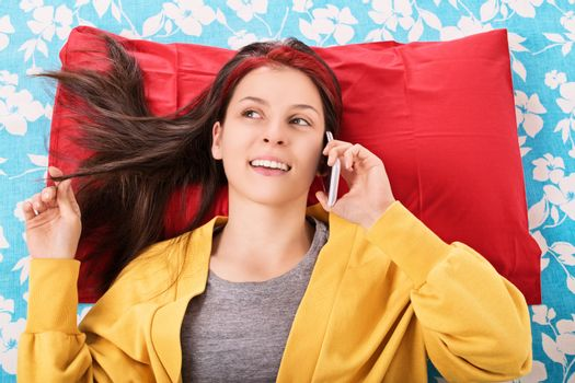 Communication, friendship concept. Beautiful young woman lying in bed, playing with her hair and talking on the mobile phone. Young girl in bed smiling and talking on the phone.