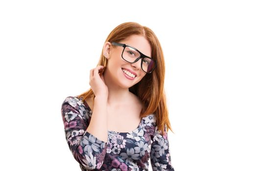 Portrait of a beautiful smiling young hipster girl in colorful casual clothes with glasses, looking timidly into the camera, isolated on white background.