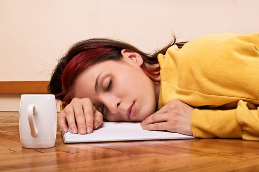 Young woman sleeping on an open notebook on the floor with a cup of coffee next to her. Beautiful young brunette student girl fell asleep on the floor preparing for an exam.