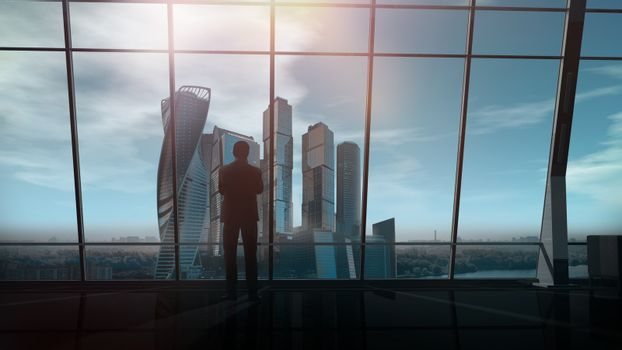 Businessman in a spacious office overlooking a business center.