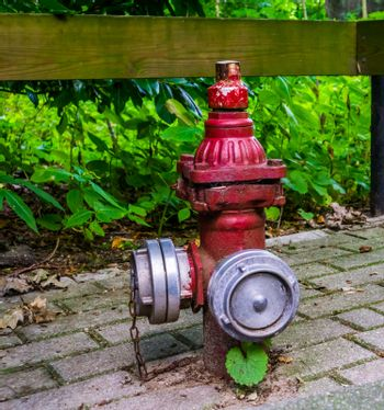Retro fire prevention system, Red fire hydrant with multiple hose fittings, outdoor safety