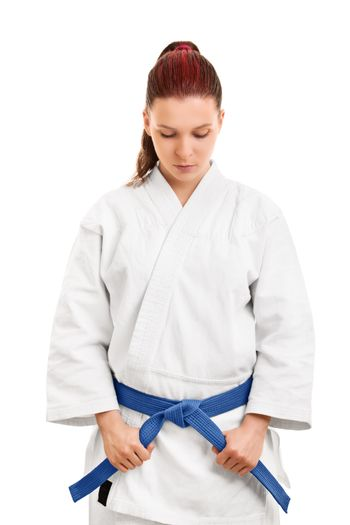Portrait of a young female martial arts fighter in a white kimono holding her blue belt and looking down, isolated on white background. Concentrating before the fight. Giving respect concept.