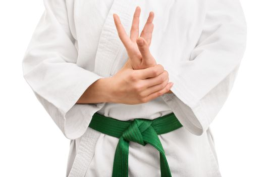 Mid section of a martial arts fighter in white kimono with green belt stretching and twisting her hand, isolated on white background.