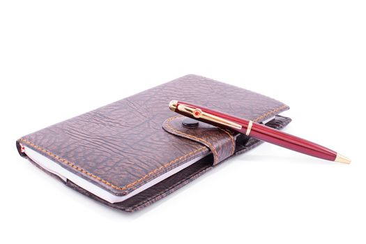 Close up shot of a leather planner notebook with a pen , isolated on white background.