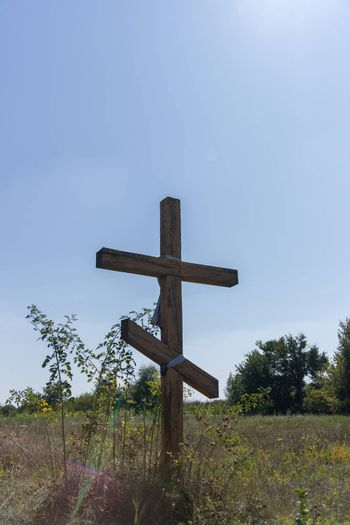 A wooden cross in the middle of the field. Christian symbol.
