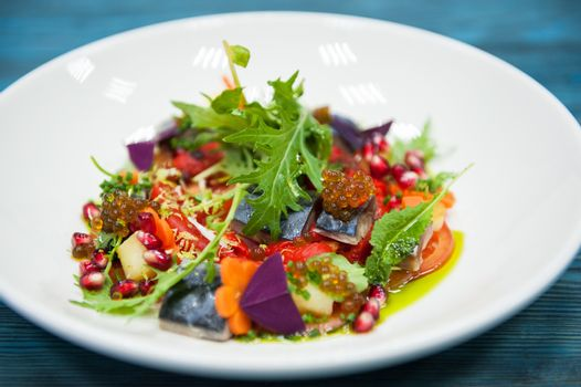 Escabeche fish dish with caviar: mackerel in marinade with vegetable, on a plate on the wooden blue background.