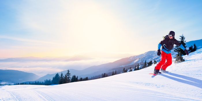 Snowboarder Riding Red Snowboard on the Free Slope in the Beautiful Morning Mountains at Sunny Weather. Snowboarding and Winter Sports