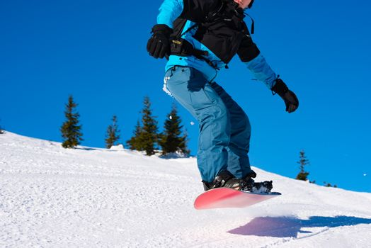Snowboarder Jumping over Slope on the Red Snowboard in the Mountains at Sunny Day. Extreme Snowboarding and Winter Sports.