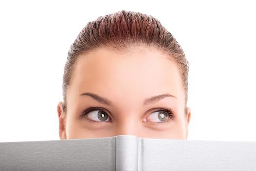 Close up shot of a pretty young girl hiding behind an open book looking away, isolated on white background.