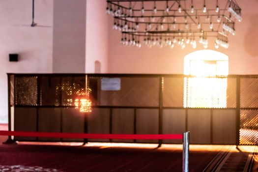 a blurry shoot from inside of a mosque - there is good looking antique chandelier and lights coming inside from window. photo has taken at izmir/turkey.