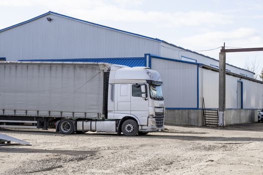 Modern trucks of various colors and models are involved for the transportation of different kinds of commercial goods are in a row on truck stop in anticipation of the continuation of working flights.