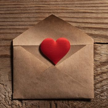 Valentine day love letter, envelope of craft paper with red heart on wooden background