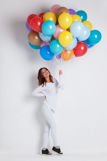Young pretty woman in white clothes with colored balloons on white background with copy space for text