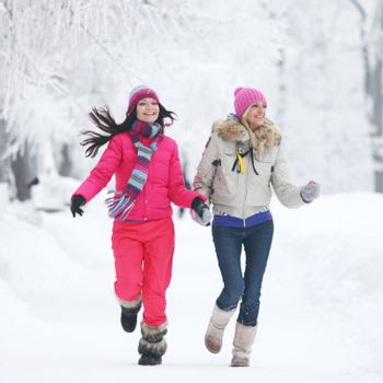 Two young happy smiling women running in the winter park