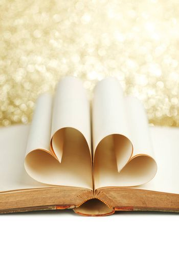 Blank pages of open book rolled in heart shape on glitter background
