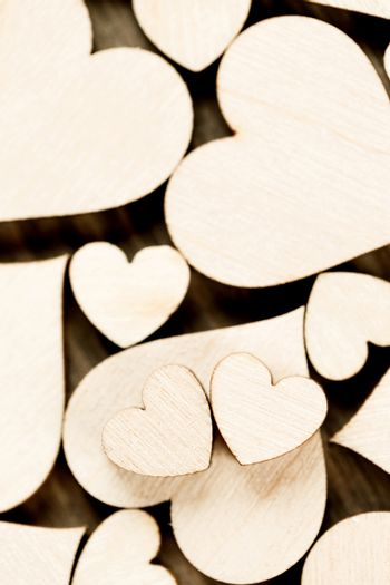 Many wooden colorless hearts background, two special ones true love concept