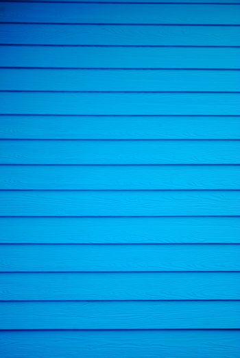 Blue painted wooden house wall. Blue plank background.