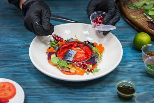 Process of cooking escabeche fish dish with caviar: mackerel in marinade with vegetable, on a plate on the wooden blue background.