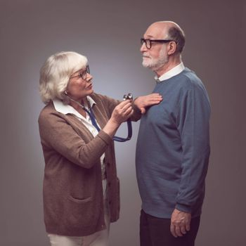Senior woman taking care of husband, checking heart beat with stethoscope