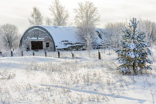 An old abandoned hangar covered in snow in the village