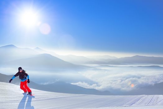 Snowboarder Riding Red Snowboard on the Slope in the Mountains in Bright Sun. Snowboarding and Winter Sports Concept.