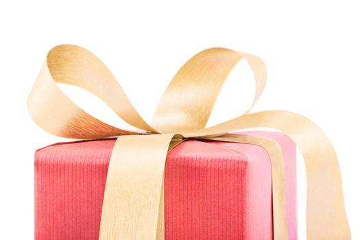 Close up of a gift box wrapped in red wrapping paper with gold colored bow ribbon, isolated on white background. Copy Space. Christmas, New Years and Valentine's day concept.