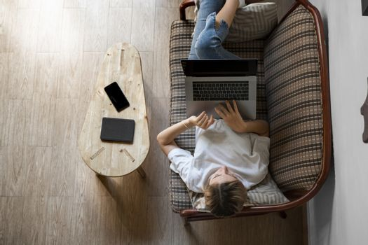 Woman with a laptop laying on a sofa. Study and work online, freelance. Self employed woman, girl working with her notebook laying on a couch with a phone, smartphone and ereader on table.