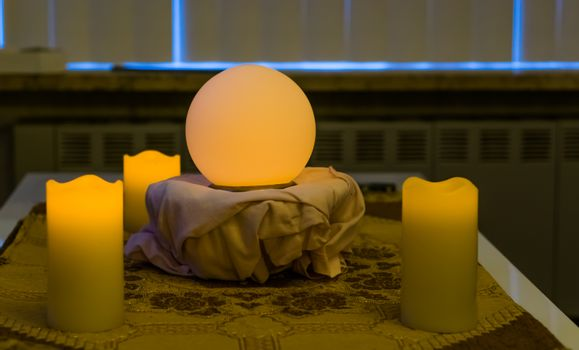 glowing fortune teller sphere with lighted candles, spiritual and witchcraft background