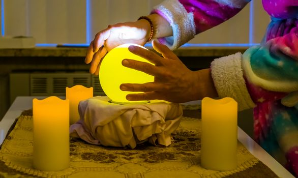fortune teller moving hands around a lighted sphere, traditional spirituality and witchcraft