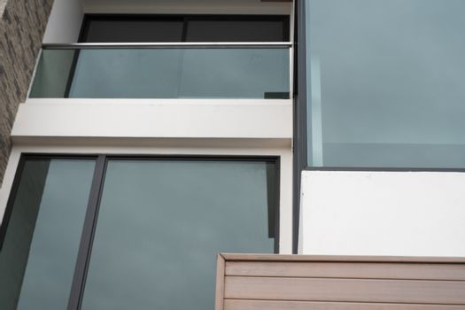 Windows of modern apartment buildings exteriors in cloudy day.